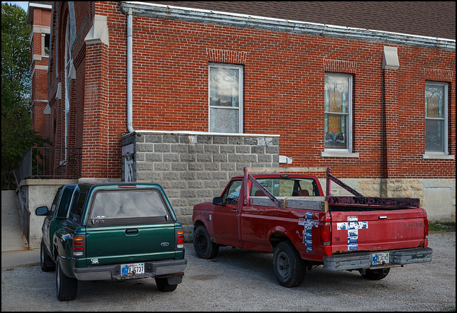 Two pickup trucks in the parking lot of 1st United Methodist Church in the small town of Warren, Indiana. One truck is decorated with crosses made from labels from water bottles from a local company called DeWeese Purified Water.