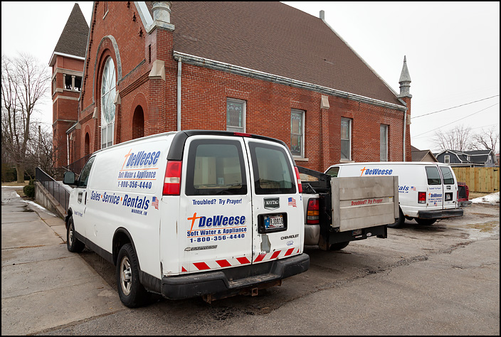 Vans and trucks from DeWeese Appliances parked next to a church in the small town of Warren, Indiana. They have a cross and the company slogan painted on them. Troubled? Try Prayer!