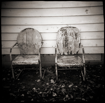 Dreamy photograph of a pair of rusty old motel chairs next to an old house. Made with a toy camera.