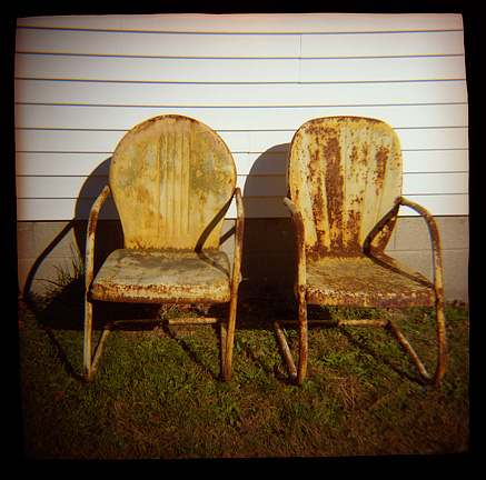 A pair of rusty old yellow motel chairs next to an old house photographed with a Diana toy camera.