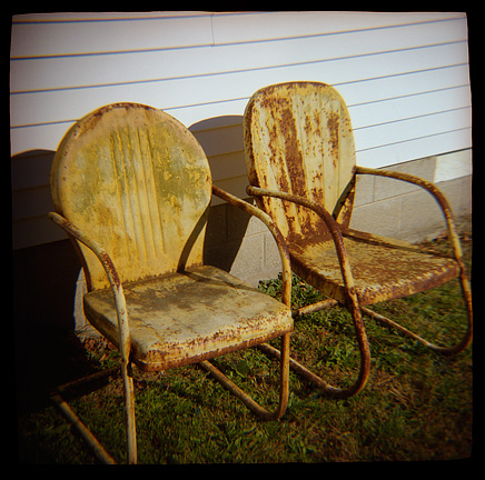 Toy camera photograph of a pair of rusty old motel chairs next to an old house.