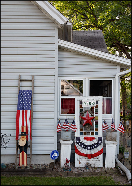 A house decorated with several small American flags, patriotic bunting, and a wooden Uncle Sam on Dinnen Avenue in Fort Wayne, Indiana.