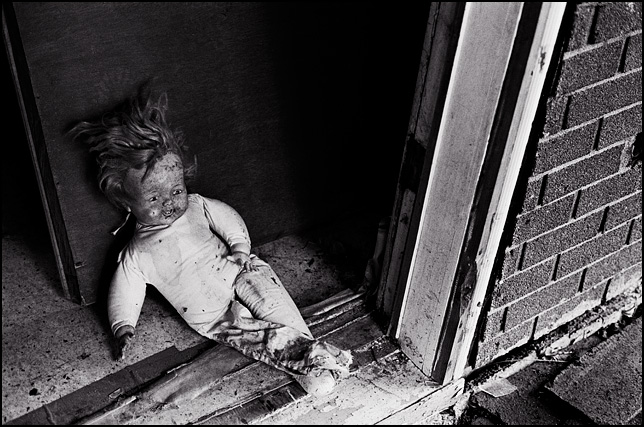 A filthy doll with one leg sits in the front doorway of an abandoned house.