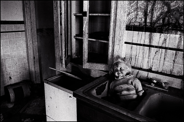 A Cricket Doll sits in the kitchen sink of an abandoned house.