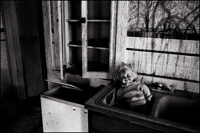A smiling Cricket Doll sits in the kitchen sink at an abandoned house.