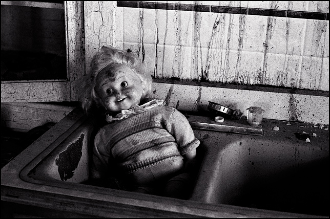 A broken old Cricket Doll in the kitchen sink in an abandoned house.