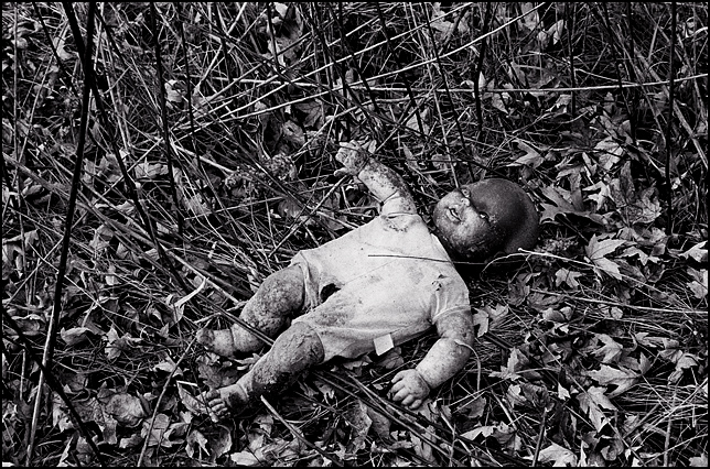An old burned doll on the ground surrounded by tall weeds and old tires behind an abandoned house.