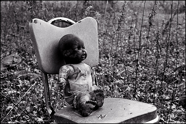 A torn up old doll with its face blackened by dirt sits on an old kitchen chair surrounded by tall weeds behind an abandoned house. The doll looks burned.