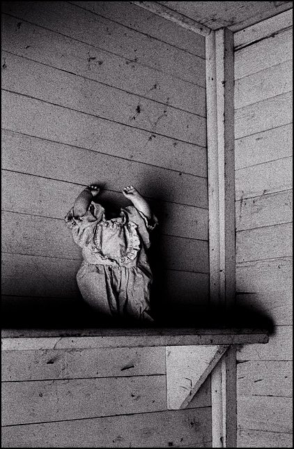 A headless doll with her hands in the air stands on a shelf in the dark basement stairwell of an abandoned house.