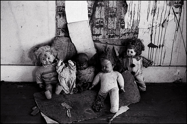 A group of forgotten old broken dolls gathered for a group portrait in the abandoned house where they live.