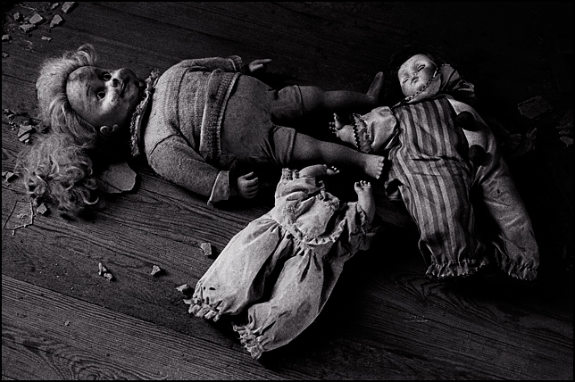 Three broken dolls on the wooden floor of an abandoned house. One is a Cricket Doll, one is a Clown Doll, and the last one is a headless doll.