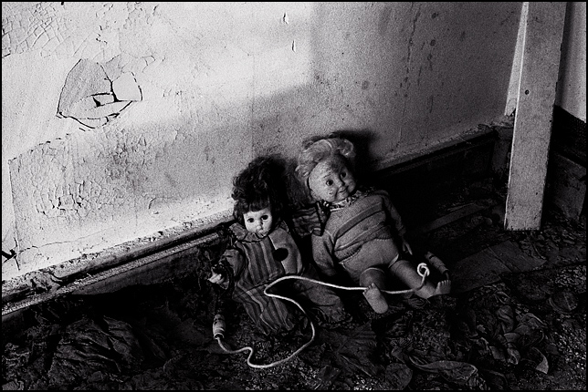 A Cricket Doll and a clown doll sit together on the filthy floor of an abandoned house holding a jump rope.