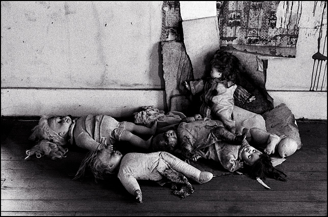 Seven broken old dolls scattered on the floor under peeling wallpaper in an abandoned house.