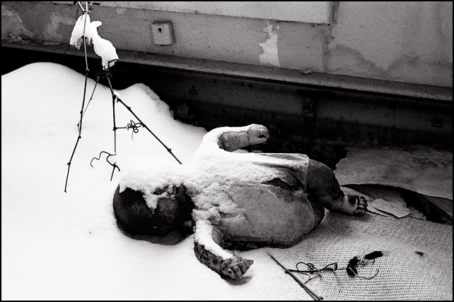An old baby doll lies like a corpse on the floor of an abandoned house with snow covering his face.