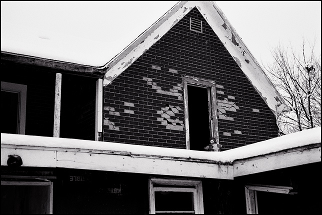 A clown doll looks out of the upstairs window of an abandoned house on a snowy winter day.