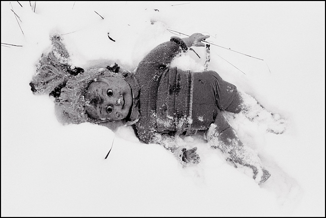 A lost Cricket Doll on her side in the deep snow behind an abandoned house.