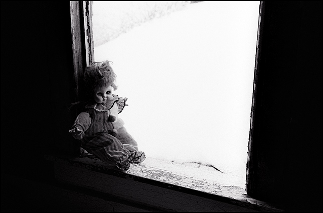A clown doll sits in the window of an abandoned house on a snowy winter day.
