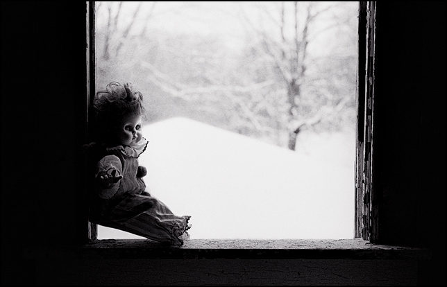 A clown doll looks out the window of an abandoned house in the winter.