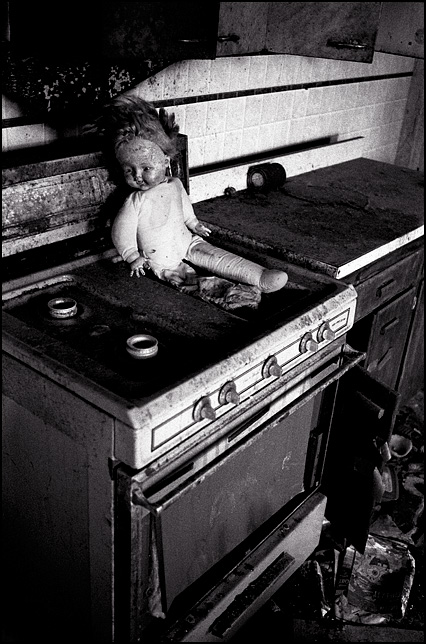 A torn up doll sits on the rusty stove in the trashed kitchen of an abandoned house.