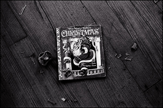 A torn up children's book on the floor of an abandoned house with a dirty old pacifier on the ground next to it. The book is a Little Golden Books story called The Night Before Christmas. The cover shows Santa Claus coming out of the fireplace with his bag of presents.
