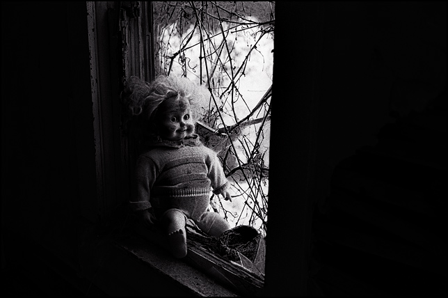 A Cricket talking doll sits in the broken window of an abandoned house next to an empty bird's nest on the windowsill.
