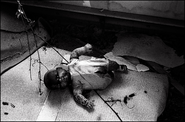 A torn up old doll with a face blackened by dirt on the squalid floor of an abandoned house.