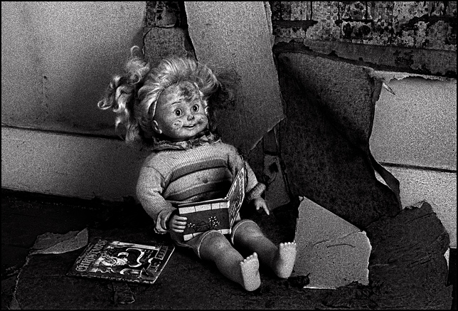 A beat up old Cricket Doll reads a children's book while sitting on rotting wallpaper on the floor of an abandoned house. A Little Golden Book called the night before Christmas sits on the ground next to her.