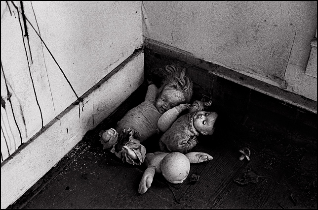 A headless doll and a Cabbage Patch Kid are stuffed into an air vent in an abandoned house with two other old broken dolls.