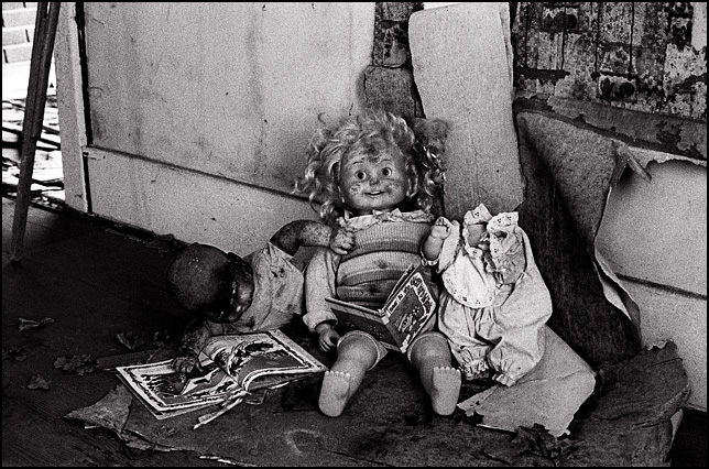 "Three old dolls sitting together in an abandoned house reading old childrens books. The Cricket doll is reading a book called ""Love is the nicest way to feel peculiar"" to a headless doll while a baby doll is reading a Little Golden Books volume entitled ""The Night Before Christmas""."