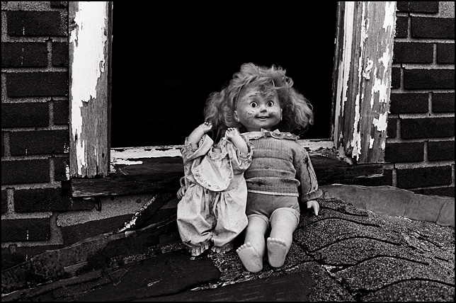 A Cricket Doll sitting with her arm around a headless doll on the roof of an abandoned house in front of a broken window.