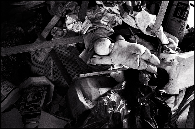 A Cabbage Patch Kid Doll lies on a pile of trash on the floor of an abandoned house.