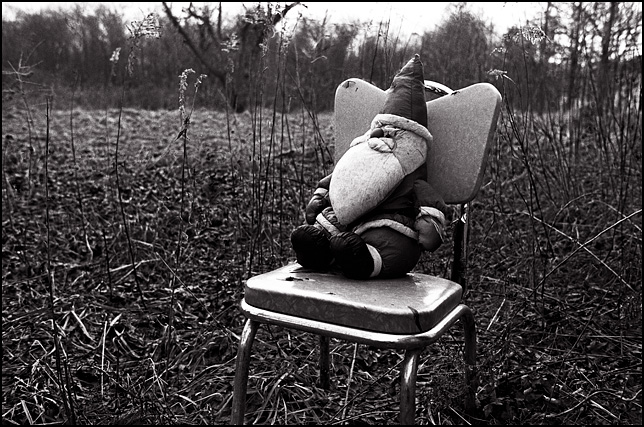 A Santa Claus doll sitting on an old metal chair surrounded by tall weeds behind an abandoned farmhouse in Indiana during the winter.