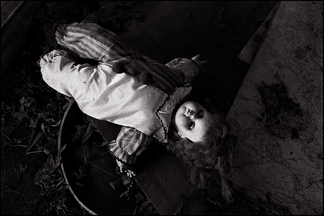 A clown doll with closed eyes laying on the floor of an abandoned house surrounded by trash.