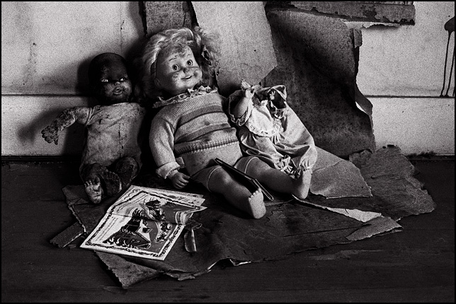A Cricket doll and two other old broken dolls sit together reading a children's book about Christmas in the bedroom of an abandoned farmhouse in front of a wall covered in peeling wallpaper.