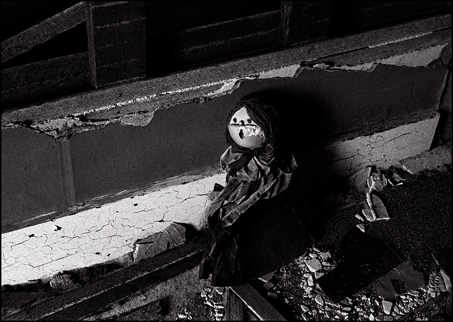 A doll with a styrofoam head leans against a broken lath and plaster wall in an abandoned farmhouse in Indiana.