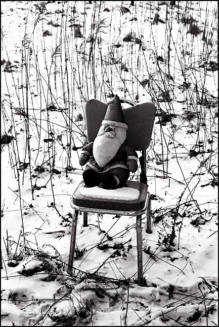 A stuffed toy Santa Claus doll sits on a snow covered chair in a field of tall dead weeds in winter.