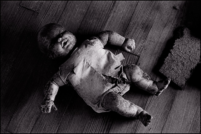 A doll baby with a burned face and dirty clothes lies like a corpse on the wood floor of an abandoned house.