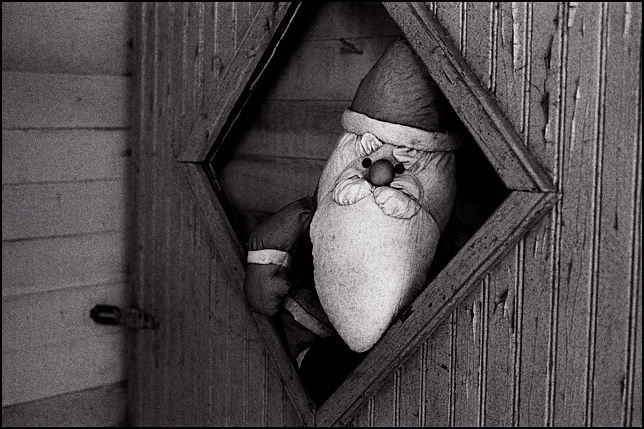A Santa Claus doll looks through the broken window of the basement door inside an abandoned house.