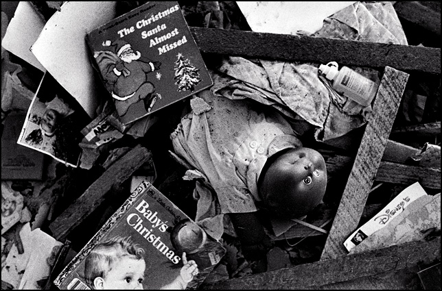 A black Cabbage Patch Kid doll in a pile of lath boards and trash on the floor of an abandoned house, surrounded by childrens books about Christmas. One book is titled BABY'S CHRISTMAS, and the other is called THE CHRISTMAS SANTA ALMOST FORGOT. A photograph of a 9 month old baby named Jessica Rose Shuster sticks out of the mound of garbage.