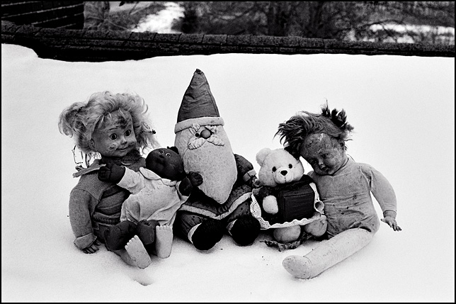 Five old broken dolls sit together in the snow on the roof of an abandoned house in Indiana. There is a Cricket doll, a Cabbage Patch Kid, a Santa Claus doll, a badly worn doll baby, and a Teddy Bear holding a gift.