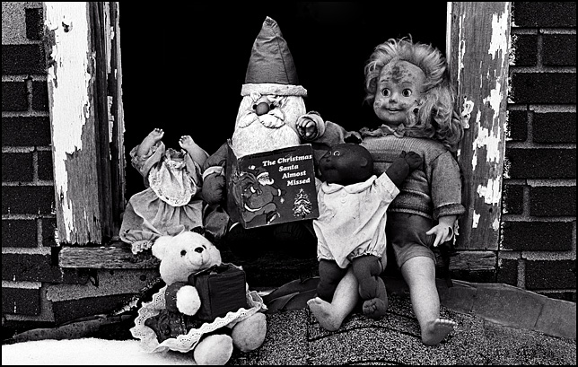 A Santa Claus Doll reads a book to a Cabbage Patch Doll, a Teddy Bear, a Headless Doll, and a Cricket Doll on the roof of an abandoned house. The title of the book is The Christmas Santa Almost Forgot.