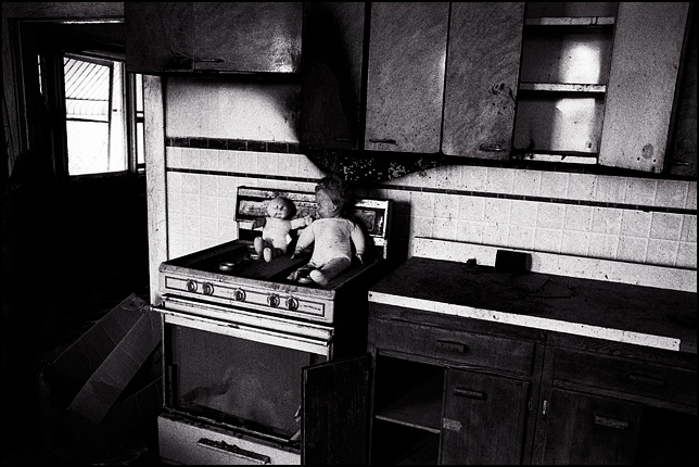 A Cabbage Patch Kid and another torn up doll sit on the rusty stove in the trashed kitchen of an abandoned house.
