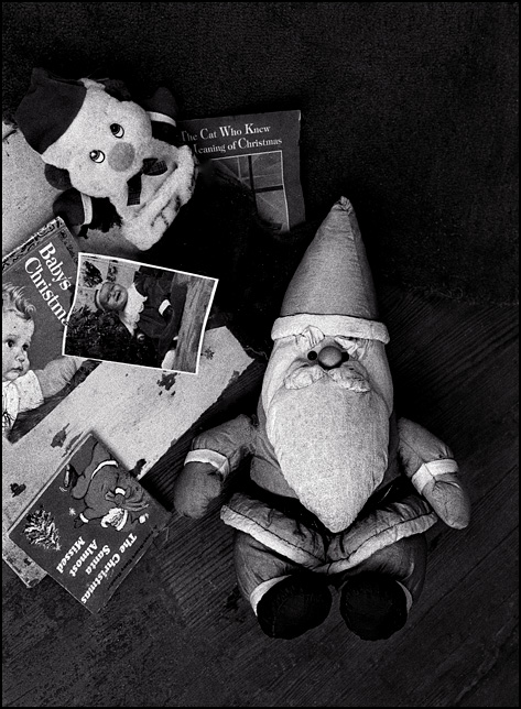 A Santa Claus doll and a toy snowman on the floor of an abandoned house surrounded by childrens books about Christmas and a baby picture of a 9 month old girl named Jessica Rose Shuster. The house is on Lima Road just outside Fort Wayne, Indiana.