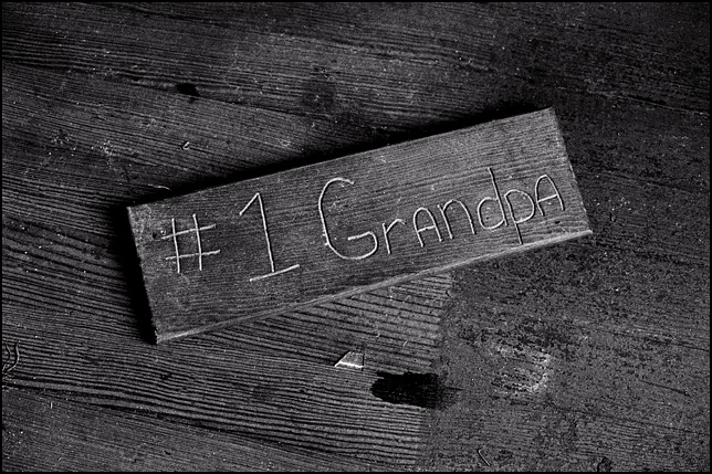 A handmade wooden sign that says #1 Grandpa, left on the floor of an abandoned house.