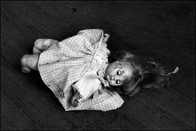 A doll baby in a frilly gingham dress sleeping with her eyes closed on the weathered wood floor of an abandoned house.