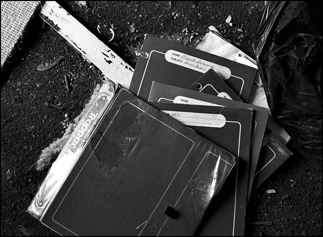 A Mead Trapper Keeper binder and folders scattered on the dirty floor of an abandoned house. The name of a child named Derek Garwood is written on the folders.