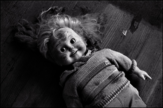An old talking Cricket Doll on the floor of an abandoned house.
