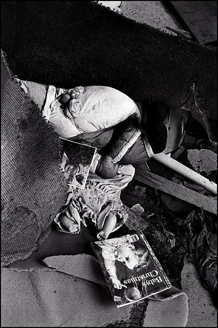 A Santa Claus doll and a headless baby doll surrounded by torn-up carpet and debris on the floor of an abandoned house. A portrait of a little girl named Jessica Rose Shuster is stuck in the pile of trash near the Santa doll.
