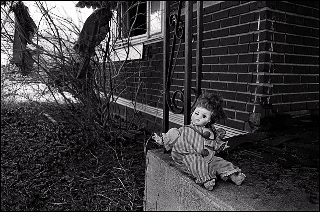 A clown doll sits alone on the front porch of an abandoned house.