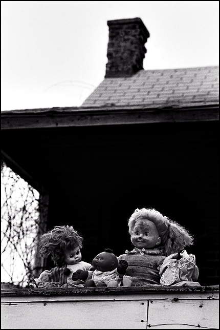 A group of old broken dolls sit together on the roof of an abandoned house. There is a Cricket Doll, a Cabbage Patch Kid, a headless baby doll, and a clown doll.